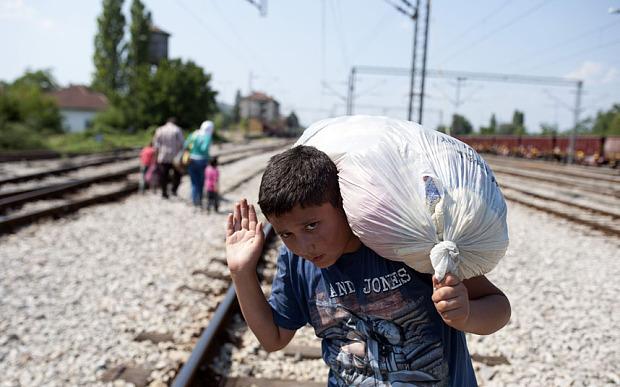 Migrants walk on train tracks towards th