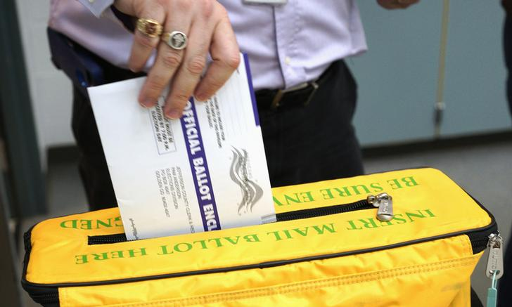 A voter deposits his ballot in the ballot box for the U.S. midterm elections at a polling place in Westminster, Colorado